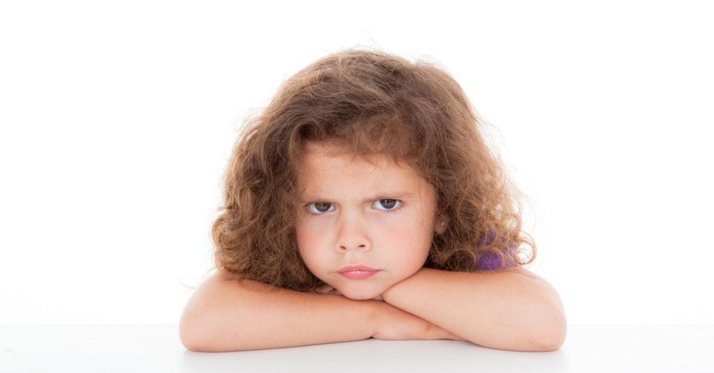 Ein verärgert wirkendes Kind lehnt auf einer Tischplatte und hat die Arme verschränkt
